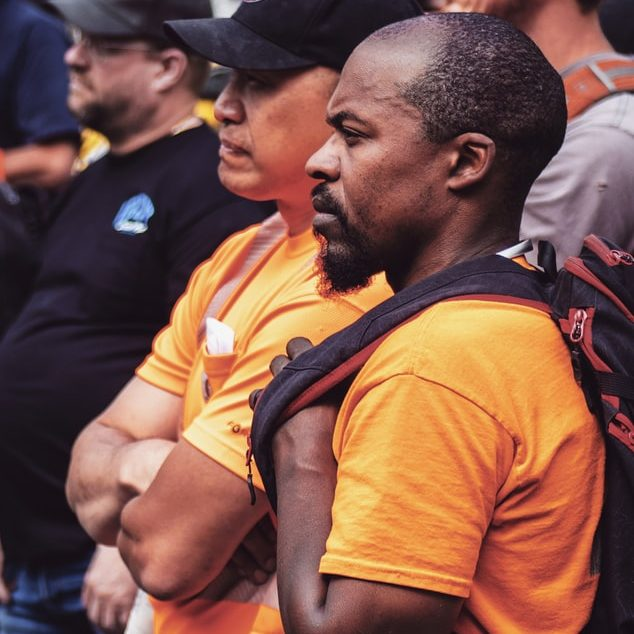Construction workers in orange shirts stand and listen